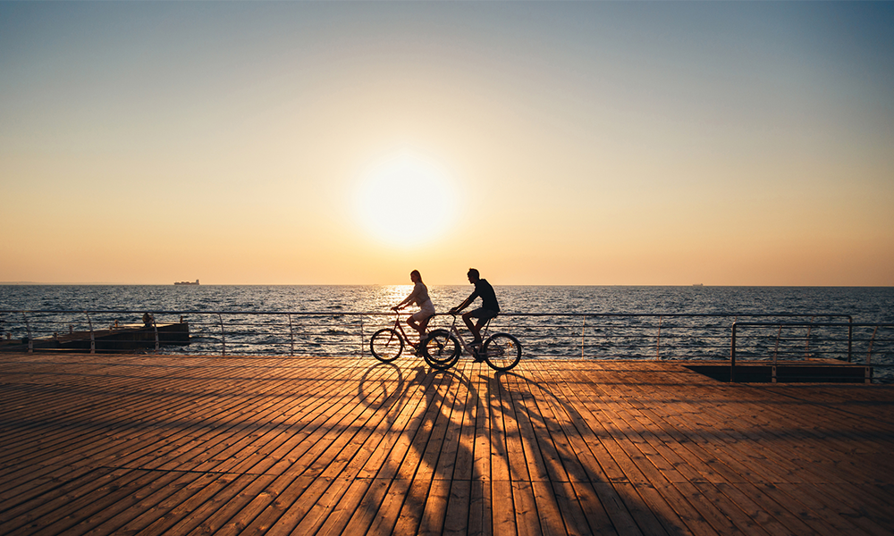 couple riding bikes on beach during sunset